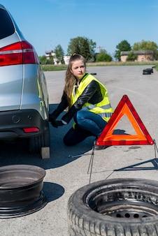 Kobieta kierowca naprawiający zmianę koła na poboczu drogi
