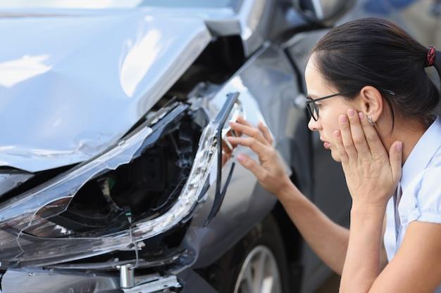 Kobieta kierowca patrzy na konsekwencje rozbitego samochodu koncepcji wypadku samochodowego