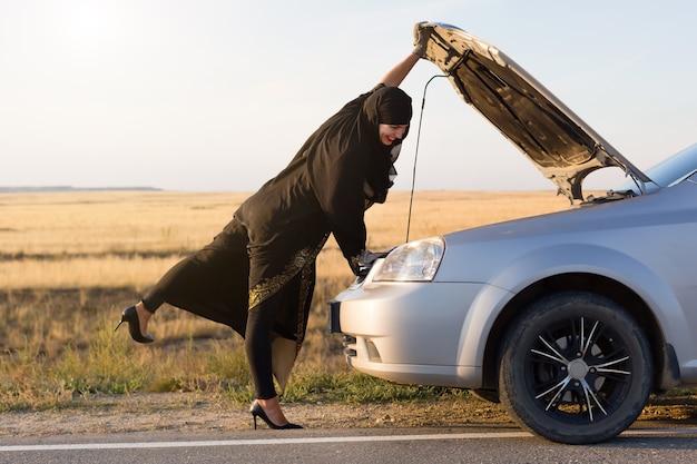 Kobieta-kierowca po raz pierwszy otwiera maskę samochodu.