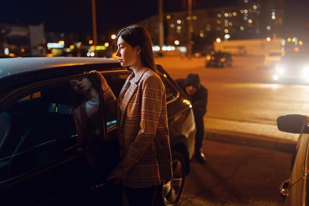 Kobieta kierowca przy samochodzie, złodziej skradający się za plecami, przestępca, kradnący.