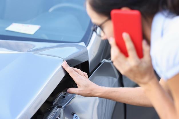 Kobieta kierowca rozmawia przez smartfon i bada uszkodzenia samochodu po wypadku dzwoniąc do