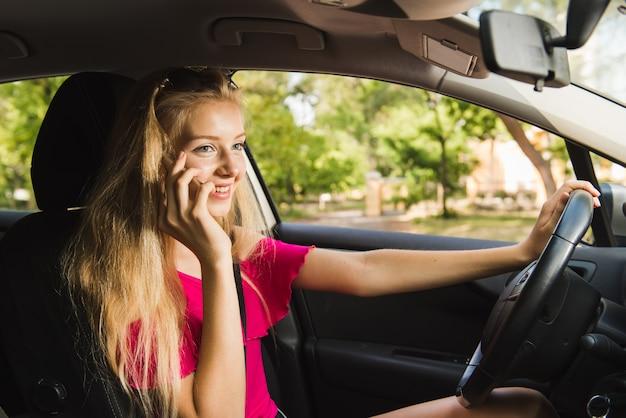 Kobieta kierowca rozmawia przez telefon komórkowy