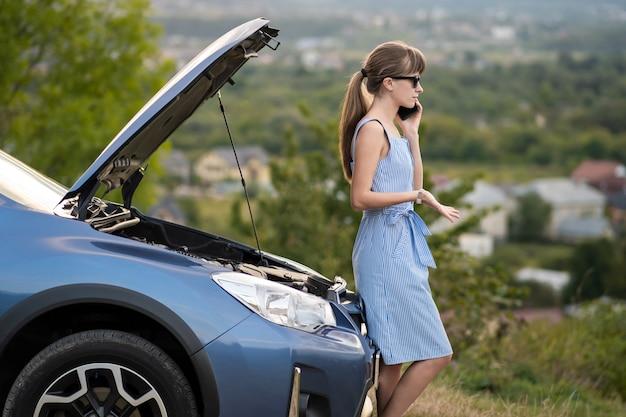 Kobieta kierowca rozmawia ze złością na telefon komórkowy z usługą pomocy