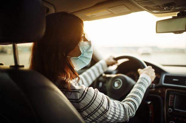 Kobieta kierowca samochodu jeździ w sterylnej masce medycznej podczas kwarantanny pandemicznej koronawirusa