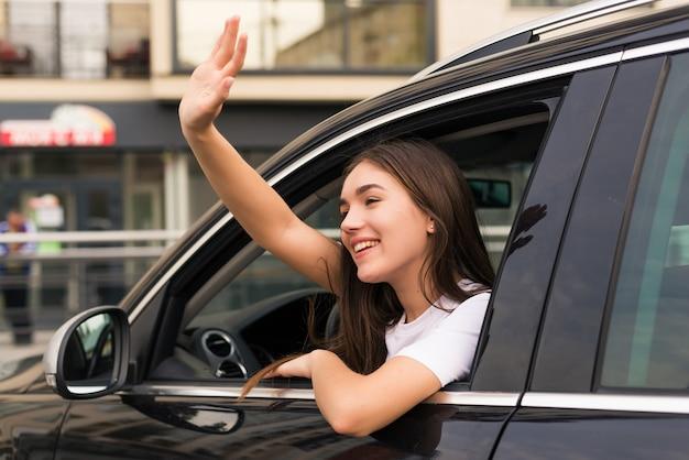 Kobieta kierowca samochodu macha na znak pożegnania na ulicy
