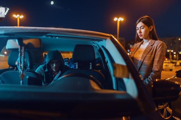 Kobieta kierowca samochodu, włamywacz na tylnym siedzeniu, przestępca, kradzież.