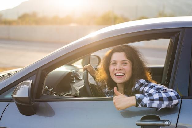 Kobieta kierowca szczęśliwy, uśmiechnięty, pokazując kciuki w górę wychodzące z niebieskiego okna bocznego samochodu na zewnętrznym parkingu. piękna młoda kobieta szczęśliwa ze swoim nowym pojazdem. pozytywny wyraz twarzy.