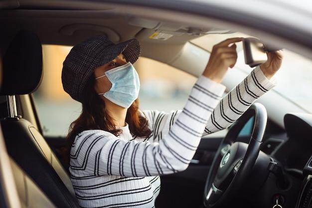 Kobieta kierowca taksówki samochodowej dostosowuje lusterko wsteczne w sterylnej masce medycznej