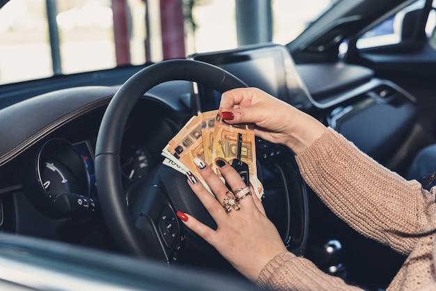 Kobieta kierowca trzyma banknoty euro i klucze na kierownicy