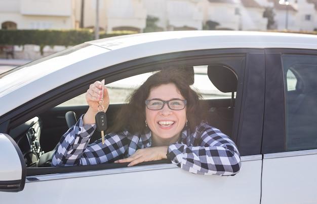 Kobieta kierowca trzymając kluczyki do samochodu, umieszczając jej nowy samochód.