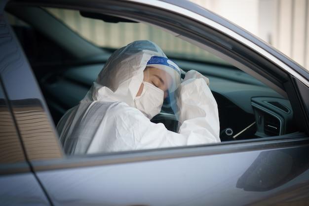 Kobieta kierowca w rękawiczkach, ochronnym kombinezonie ochronnym, osłonie twarzy i masce. wirus korony lub ochrona covid-19.