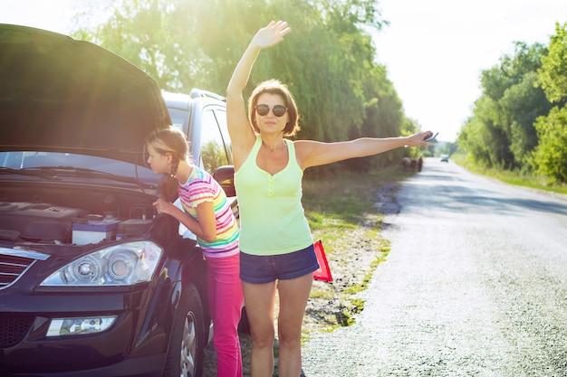 Kobieta kierowca z dzieckiem na wiejskiej drodze, w pobliżu uszkodzonego samochodu.