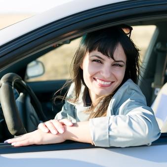 Kobieta kierowca z pięknym uśmiechem i białymi zębami.,