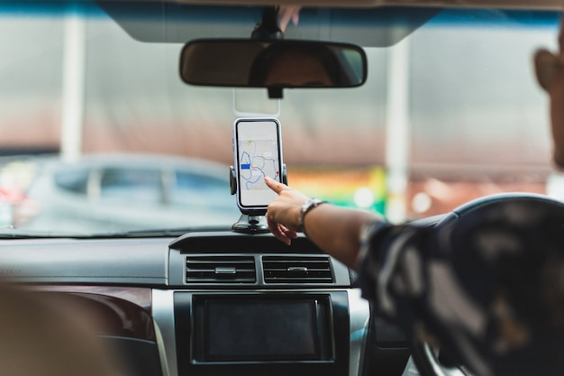 Kobieta kierowca za pomocą nawigacji gps w telefonie komórkowym podczas jazdy samochodem.