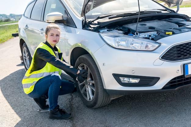 Kobieta kierowca zamierza zmienić uszkodzone koło