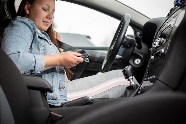 Kobieta kierowcy zapinania pasów bezpieczeństwa w samochodzie, przed wypadkiem samochodowym, koncepcja bezpieczeństwa, bezpieczny transport