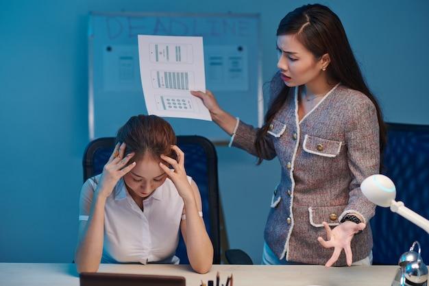 Kobieta kierownik projektu ostrzega projektanta interfejsu użytkownika za złą pracę, gdy zostaje w biurze do późna w nocy przed terminem