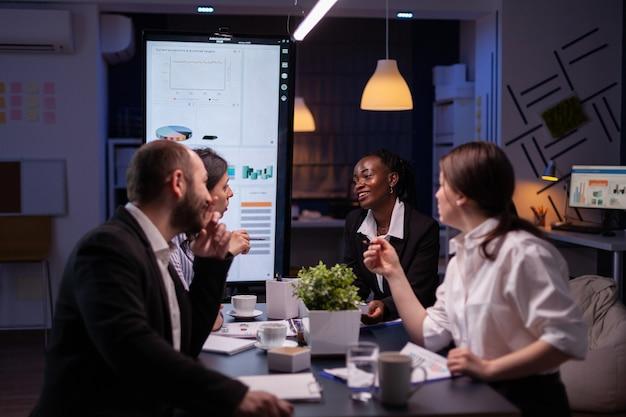 Kobieta kierownik wykonawczy wyjaśniania statystyki zarządzania pracy w nadgodzinach strategii firmy w sali konferencyjnej biura. różnorodni, wieloetniczni biznesmeni pracują zespołowo, burząc mózgi wieczorem