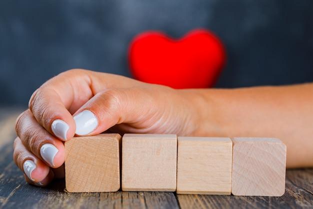 Kobieta kładąc rękę na drewnianych kostkach