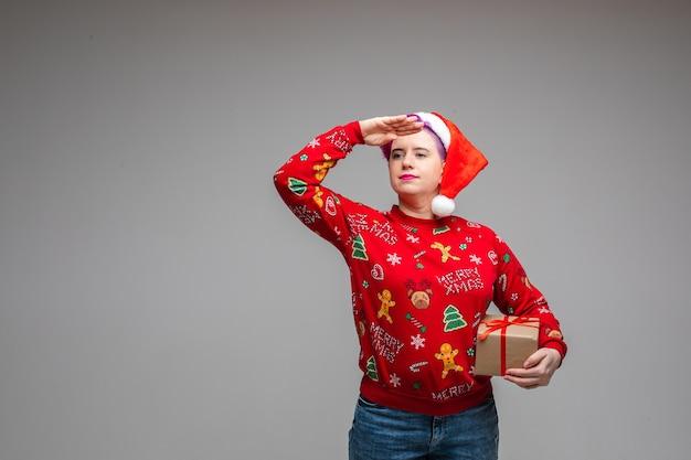 Kobieta kładąca dłoń na czole w celu zakrycia oczu podczas patrzenia z daleka i trzymania prezentu. skopiuj miejsce