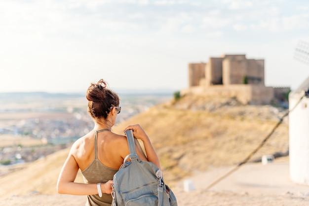 Kobieta kładąca torbę, stojąc twarzą w twarz z widokiem na zamek na wzgórzu w toledo w hiszpanii