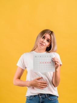 Kobieta kładzie rękę na brzuchu i pokazuje kalendarz z okresu