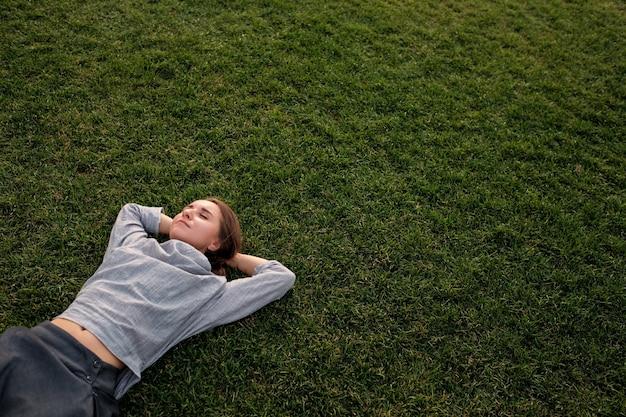 Kobieta kładzie się na trawie i odpoczywa