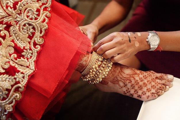Kobieta kładzie złotą bransoletkę z dzwoneczkami na malowanej nodze panny młodej