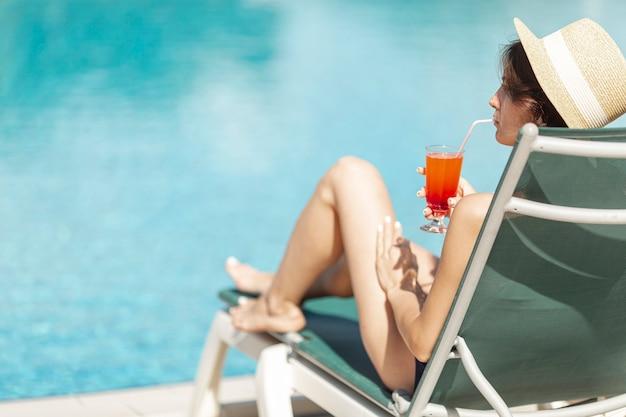Kobieta kłaść na sunbed cieszy się napoju