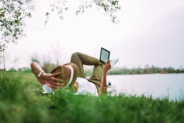 Kobieta kłaść na trawy polu i czytać e książkę.