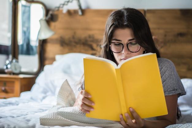 Kobieta kłaść w łóżku i czytelniczej książce