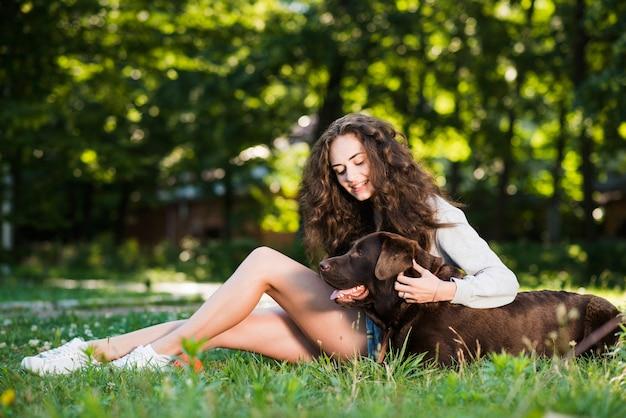 Kobieta klepie jej psiego obsiadanie na trawie w parku