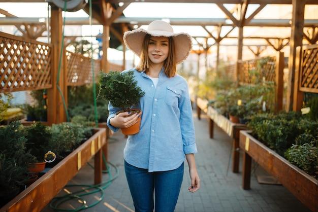 Kobieta klient kupuje kwiat w doniczce, sklep dla florystyki. kobieta wybiera sprzęt w sklepie dla kwiaciarstwa, zakup instrumentów kwiaciarni
