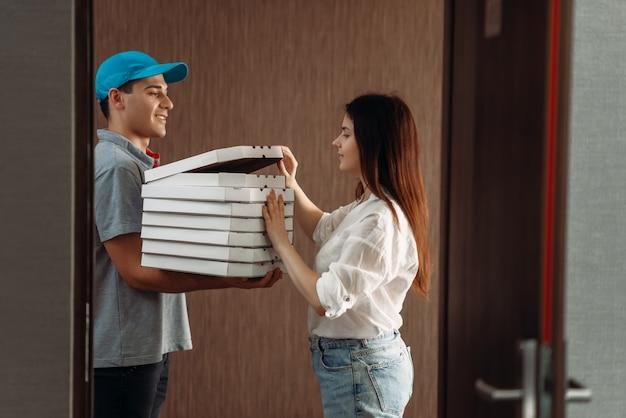 Kobieta klient na wyciągnięcie ręki i chłopiec dostawy pizzy