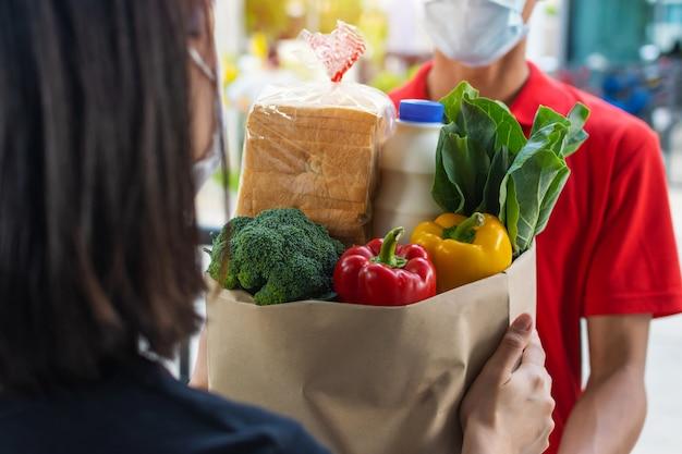 Kobieta klient otrzymujący zestaw świeżej żywności torba od dostawcy usługi dostarczania żywności człowiek z maską ochronną w czerwonym mundurze w drzwiach do domu, ekspresowa dostawa, kwarantanna, wybuch wirusa, koncepcja dostawy żywności