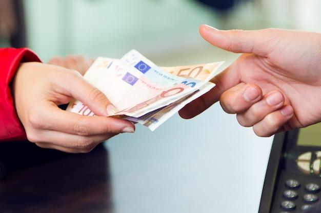 Kobieta klient płaci z pieniądze. szczegóły dłoni.