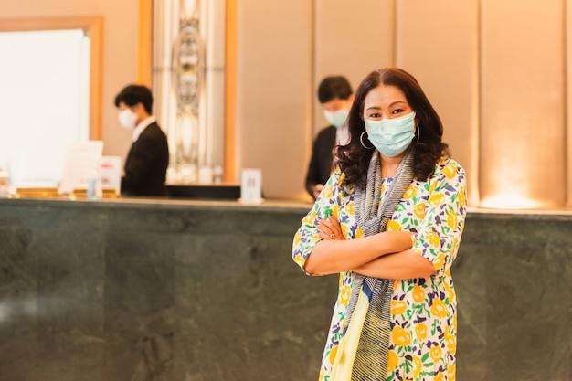 Kobieta klient sobie maskę medyczną stojąc przed recepcją hotelu.