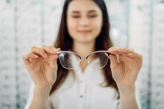 Kobieta klient trzyma w ręku okulary, sklep optyczny