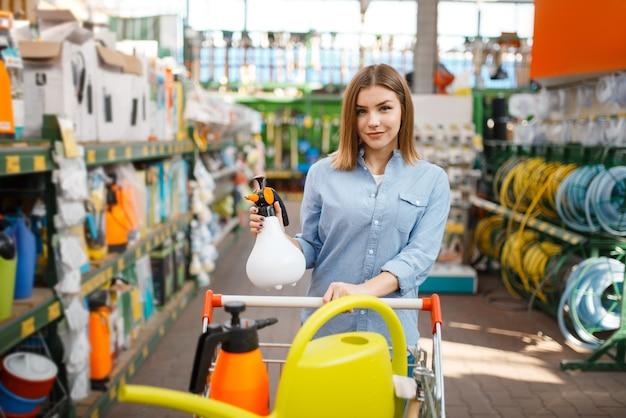 Kobieta klient wybiera narzędzia, sklep dla ogrodników