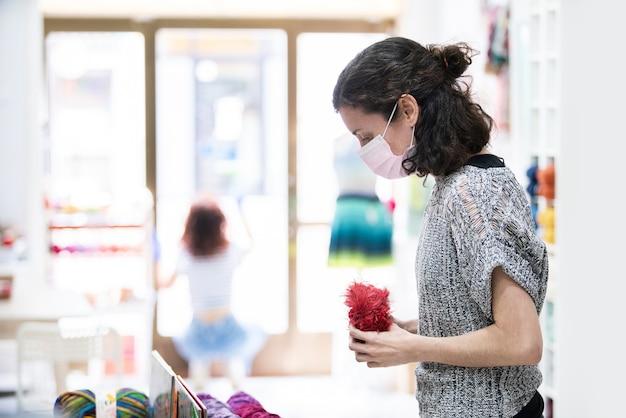 Kobieta klienta zakupy w sklepie detalicznym w masce