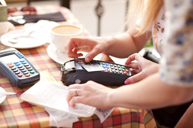 Kobieta klientka płacąca kartą kredytową w kawiarni