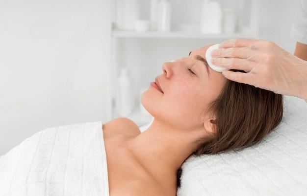 Kobieta klientka w salonie rutynowej pielęgnacji twarzy z dyskami oczyszczającymi