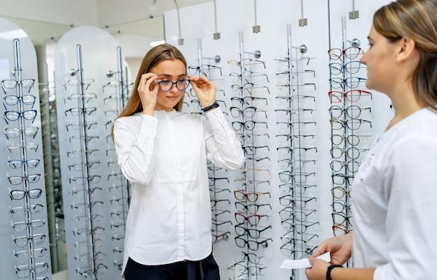 Kobieta klientka wybiera okulary korekcyjne w sklepie okulistycznym. kompetentny specjalista udziela konsultacji klientowi. sklep z okularami.