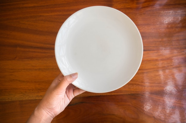 Kobieta (kobieta) trzymaj się za ręce (wsparcie) białe naczynie (tabliczka) na drewnianym stole.