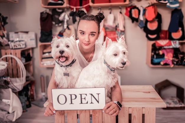 Kobieta kochająca zwierzęta. ciemnooka kobieta kochająca zwierzęta domowe czuje się niesamowicie podczas otwierania sklepu dla zwierząt