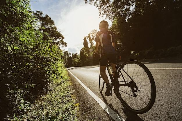 Kobieta kolarz szosowy na rowerze ścieżka w lesie i górach