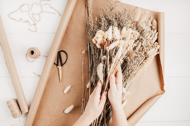 Kobieta komponująca bukiet suchych kwiatów i ziół, modna dekoracja wnętrz, pomysł na kwiaciarnię rzemieślniczą. widok z góry, układ płaski