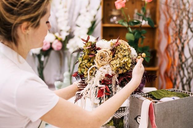 Kobieta komponuje kreatywnie bukiet w wazie