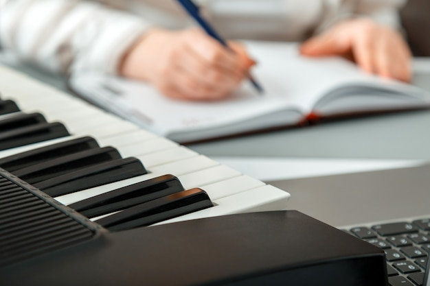 Kobieta komponuje muzykę, kobiece ręce piszą notatki lub piosenkę w księdze muzycznej. teen dziewczyna uczy się grać na pianinie, robi notatki w notesie. instrument klawiszowy z syntezatorem. edukacja muzyczna online.