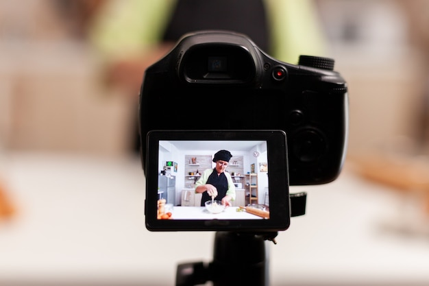 Kobieta komunikująca się z subskrybentami przez kamerę wideo podczas wyrabiania ciasta